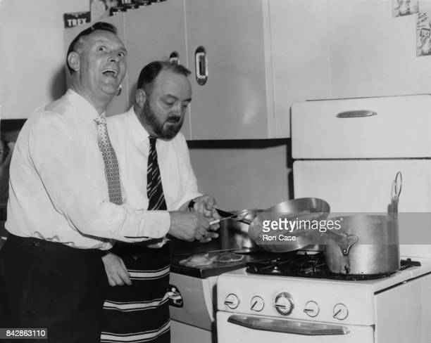 British radio comedian Al Read watches TV chef Philip Harben frying sausages at the Food Fair in Olympia London 15th September 1954 The Lancashire...
