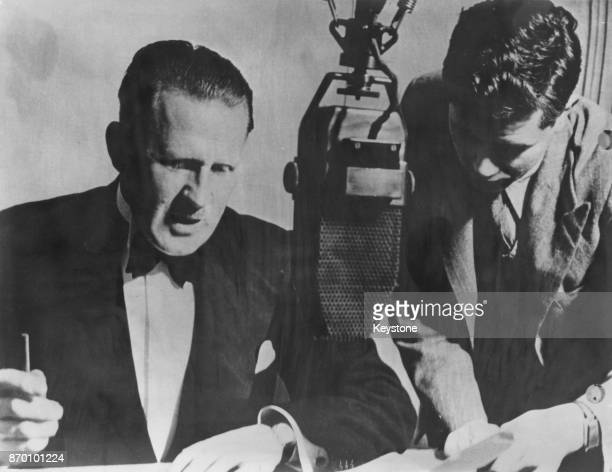 British radio personality Stuart Hibberd reads the news as Home News Editor Michael Balkwill places a new script on the table at the BBC News...