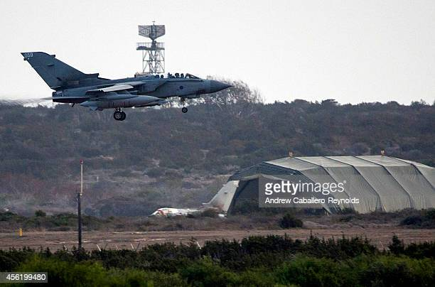 British RAF tornado fighter jets prepares to land on an airstrip as it passes by another Tornado next to a hanger at RAF Akrotiri after returning...