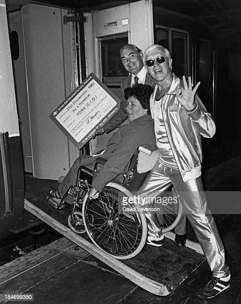 British Railways chairman Sir Peter Parker and English dj and television presenter Jimmy Savile help a wheelchair user onto a train at Euston Station...