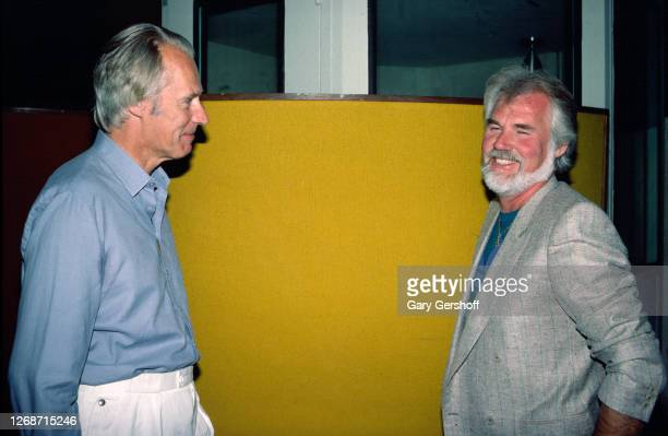 British record producer George Martin and American Country musician Kenny Rogers talk together during Roger's birthday luncheon at RCA Studios New...