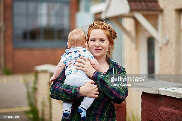 british red headed female in street holding son - single mother stock photos and pictures