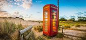 British red telephone box illuminated at sunrise on seaside beach