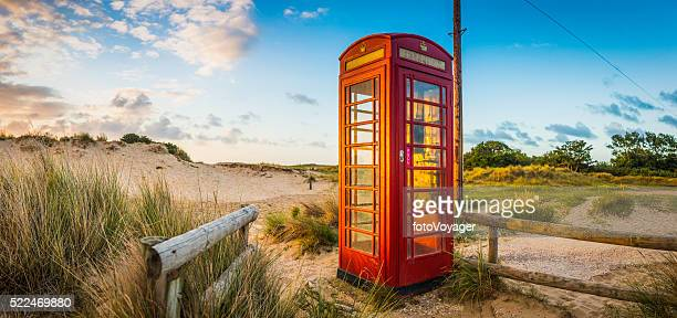 British red telephone box illuminated at sunrise on seaside beach