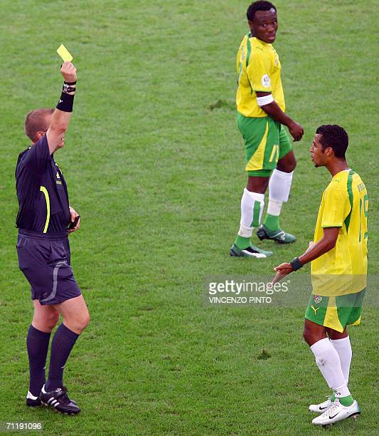 British referee Graham Poll shows a yellow card as Togolese defender Ludovic Assemoassa reacts during the FIFA World Cup 2006 group G football match...