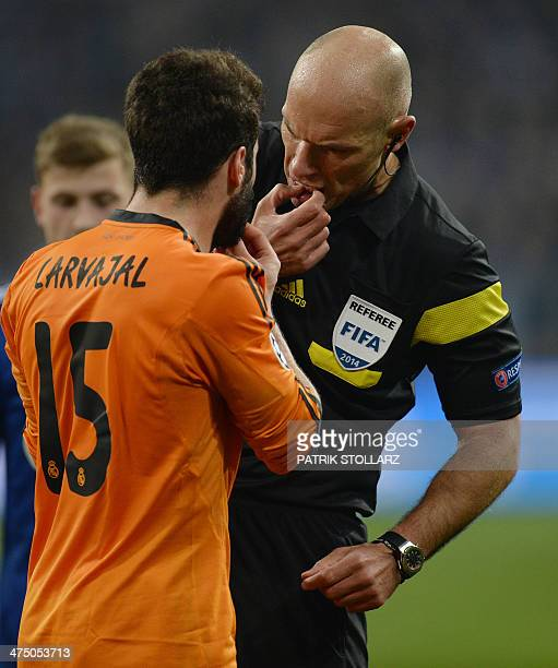 British referee Howard Webb talks to Real Madrid's defender Daniel Carvajal during the firstleg round of 16 UEFA Champions League football match...