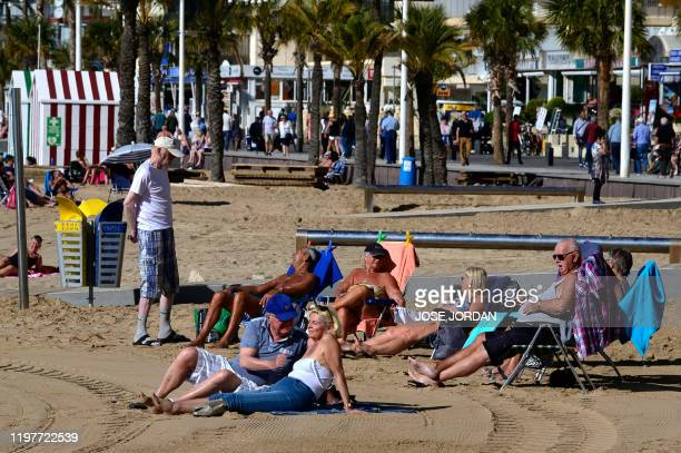 British residents and tourists bask in the sun on the beach in Benidorm on January 31 2020 On the sundrenched eastern coast of Spain British retirees...