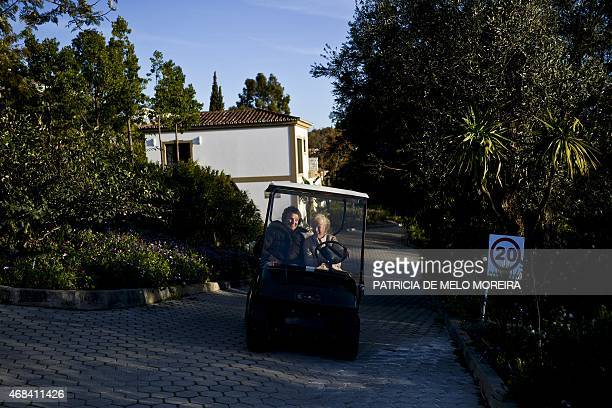 British retiree Jill Ricketts drives a golf cart accompanied by Norwegian retiree Margarette Thore at the Monte da Palhagueira British Village a...