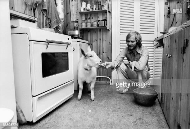 British rhythm & blues singer Long John Baldry feeding his pet goat, Mai, at home in North London, 31st October 1973.