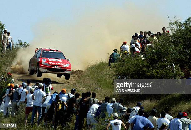 British Richard Burns and his codriver Robert Reid speed past spectators with their Peugeot 206 WRC at Agios Stefanos' special stage during the 50th...