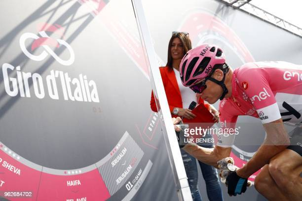 British rider and pink jersey leader Christopher Froome signs autographs before the start of the 20th stage from Susa to Cervinia in the 101th Giro...