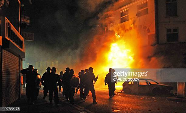 British riot police arrive in front of a burning building and burnt out car in Croydon South London on August 8 2011 Now in it's third night of...