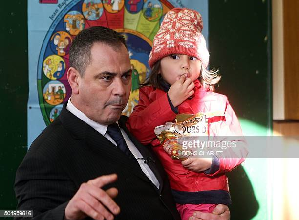 British Robert Lawrie carries four-year-old Afghan refugee Bahar Ahmadi on January 14, 2016 in Boulogne-sur-Mer prior to the start of his trial for...