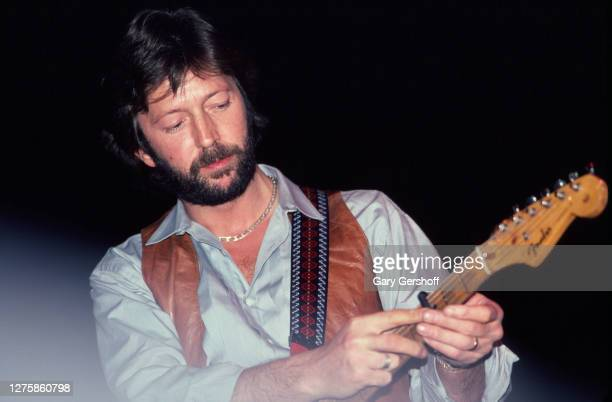 British Rock and Blues musician Eric Clapton plays guitar as he performs onstage during his 'Money and Cigarettes' tour at Brendan Byrne Arena , East...