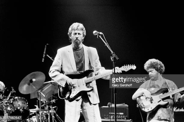 British Rock and Blues musician Eric Clapton plays guitar as he performs onstage during his 'Behind the Sun' tour at Brendan Byrne Arena , East...