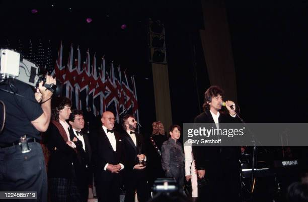 British Rock and Pop musician George Harrison speaks onstage during his induction, as a member of the group the Beatles, at the Rock and Roll Hall of...