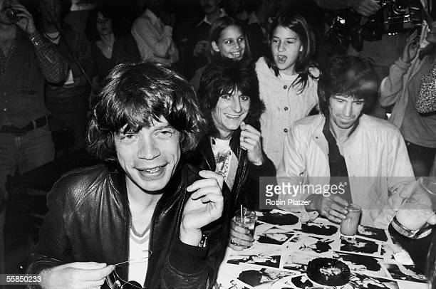 British rock and roll group the Rolling Stones sign autographs for fans at a release party at the Trax nightclub for the band's 'Love You Live' album...