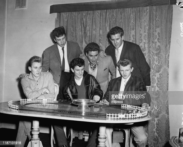 British rock and roll singers Billy Fury Marty Wilde Dickie Pride Vince Eager and Kenny Packwood playing with a toy car track with British music...