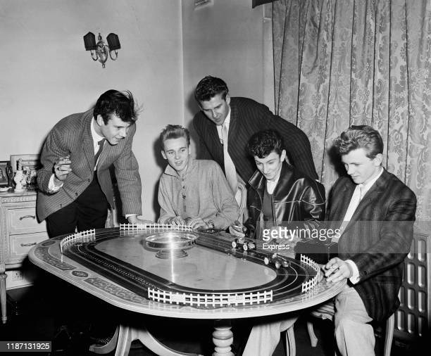 British rock and roll singers Marty Wilde Billy Fury Vince Eager Dickie Pride and Kenny Packwood playing with a toy car track UK 12th February 1959