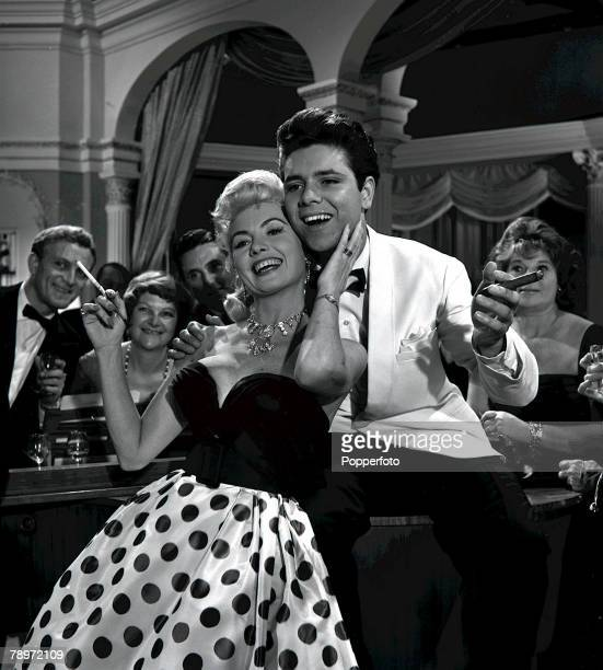 """British rock and roll star Cliff Richard holdig a cigar as he dances with actress Yolande Donlan during the filming of """"Express Bongo"""""""