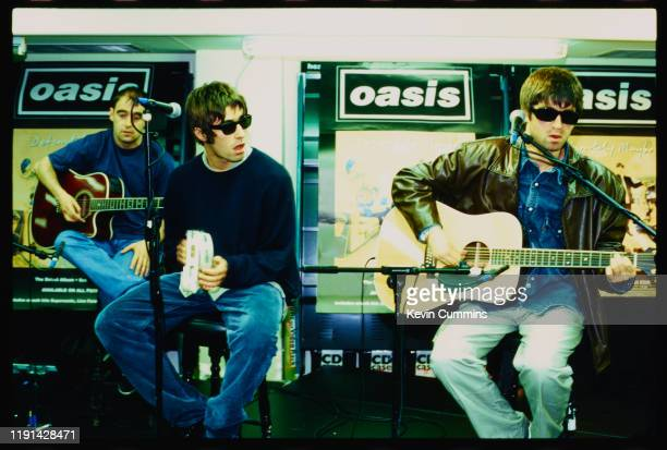 British rock band Oasis performing live at an in-store promotion gig, UK, 1994; they are Paul Arthurs, Liam Gallagher, and Noel Gallagher.