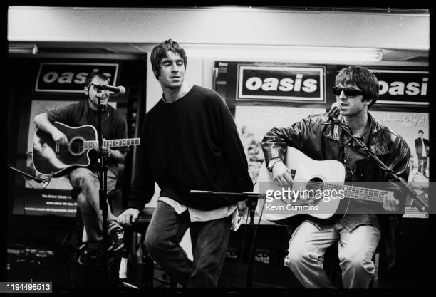 British rock band Oasis performing live at an in-store promotion gig, UK, 1994; they are Paul Arthurs, Liam Gallagher, Noel Gallagher.