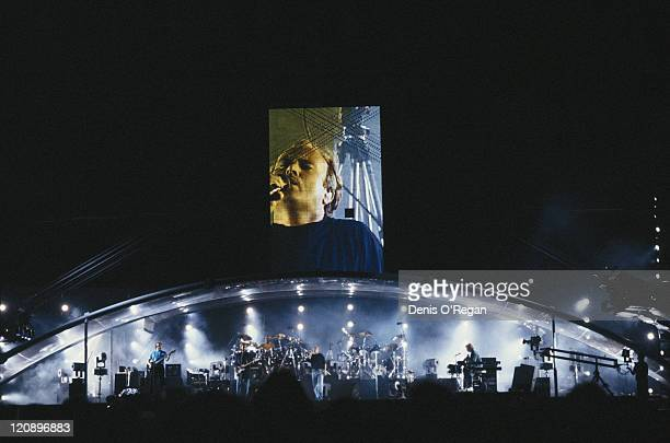 British rock group Genesis performing on stage circa 1990 Singer and drummer Phil Collins is at centre stage and projected above the stage guitarist...