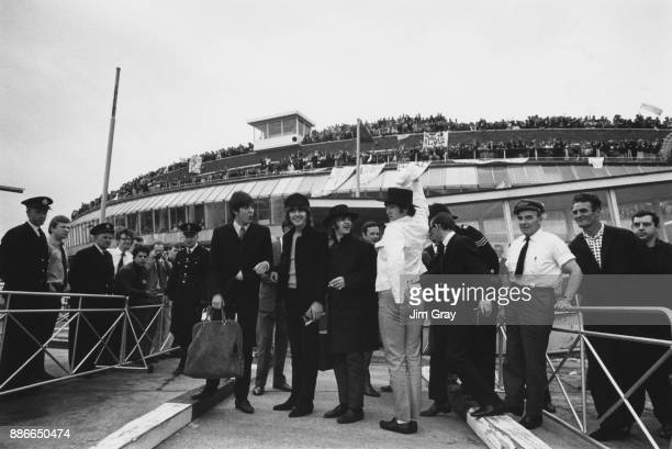 British rock group the Beatles clowning around at London Airport while fans line the roof of the Queen's Building July 1965 From left to right Paul...