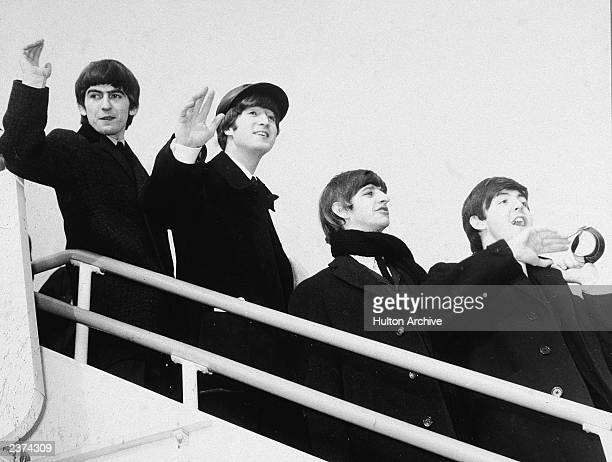 George Harrison John Lennon Ringo Starr and Paul McCartney wave as they board an airplane to begin their first American tour London England July 2...