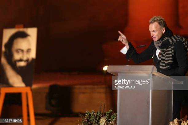 British rock icon Sting gestures as he addresses a ceremony in honour of the late Italian tenor Luciano Pavarotti whose portrait stands on an easel...