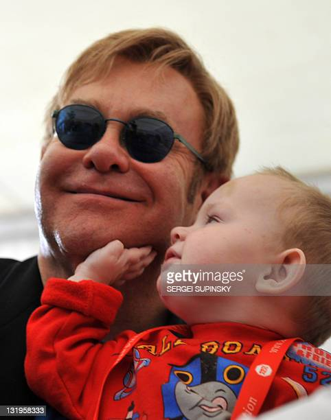 British rock legend Sir Elton John holds little Lev, a patient of a specialized orphanage for HIV-positive children after the first results of the...
