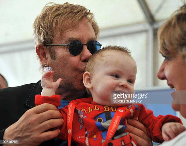 British rock legend Sir Elton John kisses little Lev, a patient of a specialized orphanage for HIV-positive children after the first results of the...
