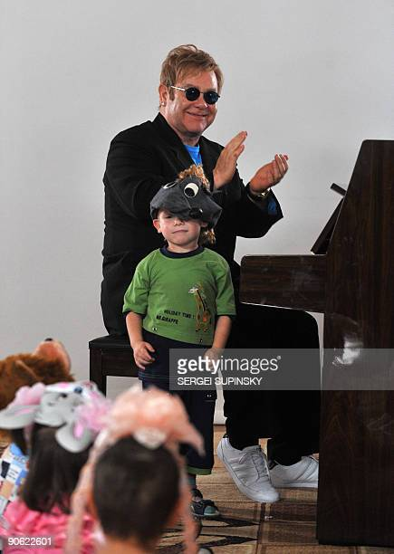 British rock legend Sir Elton John plays a song on a piano for patients of a specialized orphanage for HIV-positive children after the first results...