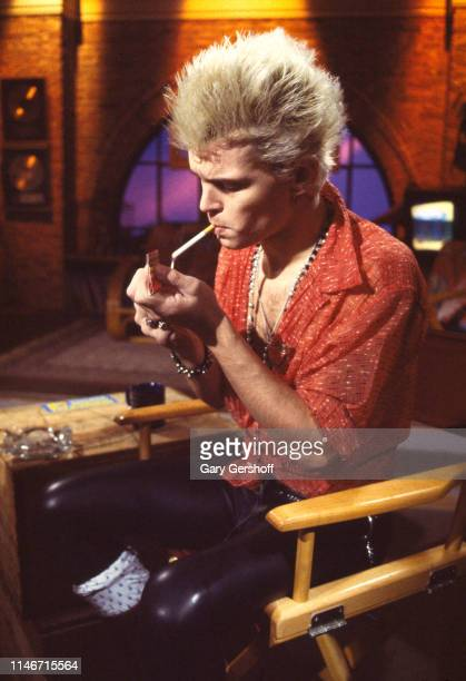 British Rock musician Billy Idol lights a cigarette during an interview at MTV Studios, New York, New York, December 6, 1982.