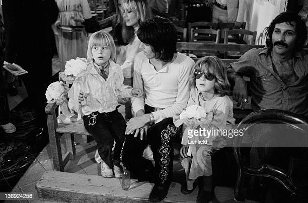 British rock musician Keith Richards sitting with children in front of his partner Italian model film actress and fashion designer Anita Pallenberg...