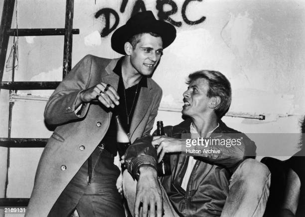 British rock singer and actor David Bowie has a drink backstage with Paul Simonon the bassist from British punk rock band The Clash following the...