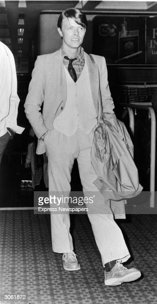 British rock singer and actor David Bowie walks at Heathrow Airport wearing a suit and sweater and holding his coat before embarking on a tour of...