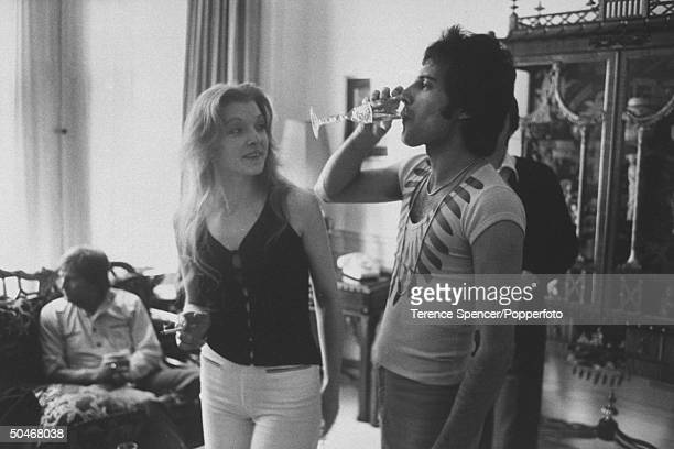 Rock singer Freddie Mercury drinking a class of champagne as his girlfriend Mary Austin looks on during party for friends at home.
