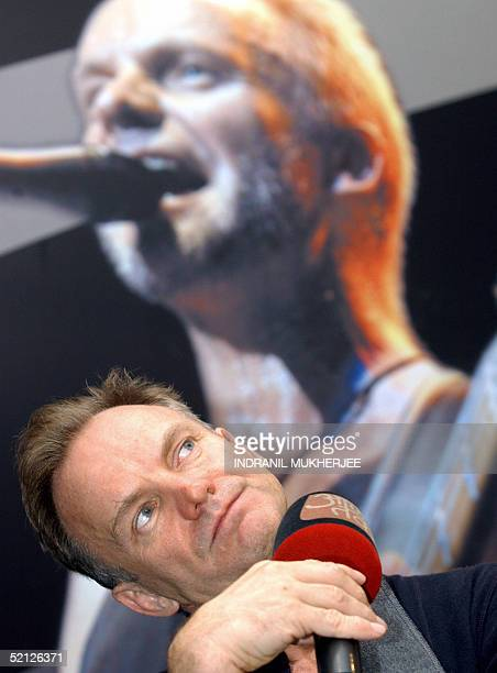 British rock singer Gordon Sumner better known as 'Sting' ponders over a question in front of a lifesize poster of himself as he addresses a press...