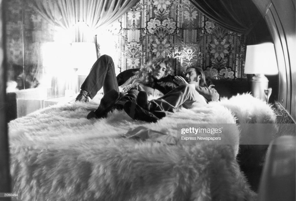 British rock singer Robert Plant (L) of the band Led Zeppelin and the group's road manager, Richard Cole, relax on a bed covered by a fur rug and discuss details of their upcoming concert, New York City, New York, July 30, 1973.