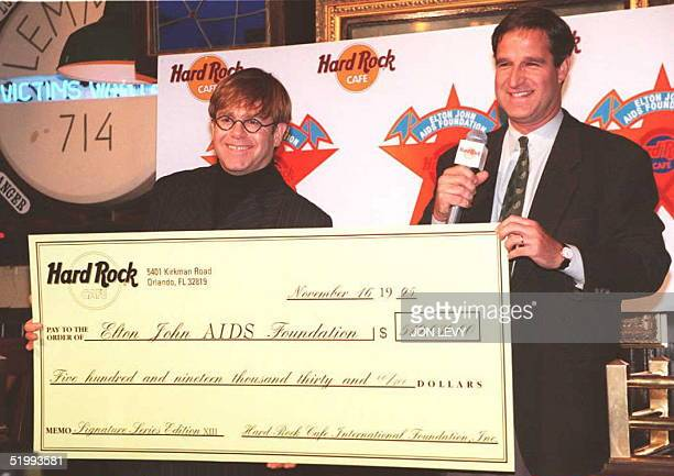British rock star Elton John and Hard Rock Cafe CEO Art Levitt hold a check for $519030 USD raised from the sale of a series of Tshirts designed by...