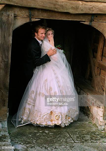 British rock star Sting holds his bride Trudie Styler blowing a kiss to the press prior to enter the church 22 August 1992 in Amesbury The couple who...