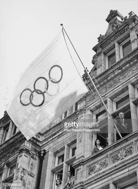 British rower Jack Beresford hoists the Olympic flag from a window of the British Olympic offices in Mayfair, London, England, 26th August 1960. The...