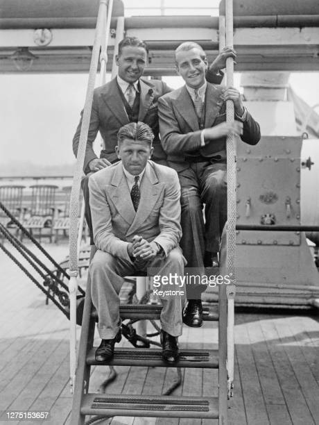British rower Ted Phelps his brother British rower Eric Phelps and German rower Georg Von Opel sitting in the steps leading to an upper deck of the...