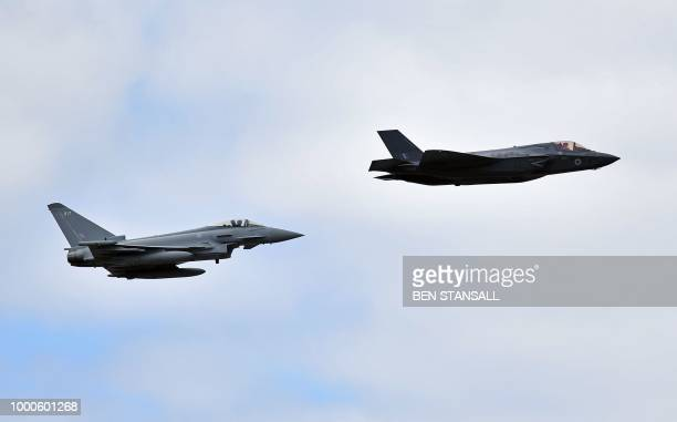 A British Royal Air Force Lockheed Martin F35 Lightning II and a Eurofighter Typhoon aircraft perform a flypast during the Farnborough Airshow south...