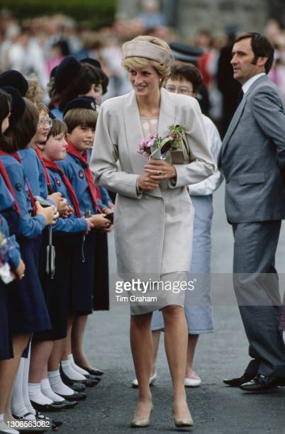 British Royal Diana, Princess of Wales , wearing a beige suit with a matching polka dot headband-style hat, carrying a bouquet of flowers as she...