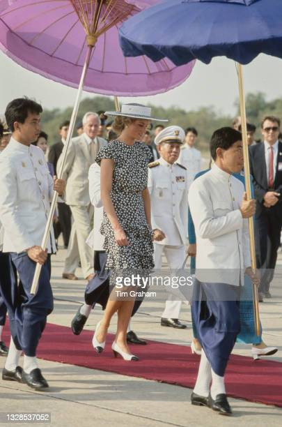 British Royal Diana, Princess of Wales , wearing a dress by Alistair Blair and a Philip Somerville hat, shielded with parasols on her arrival at...