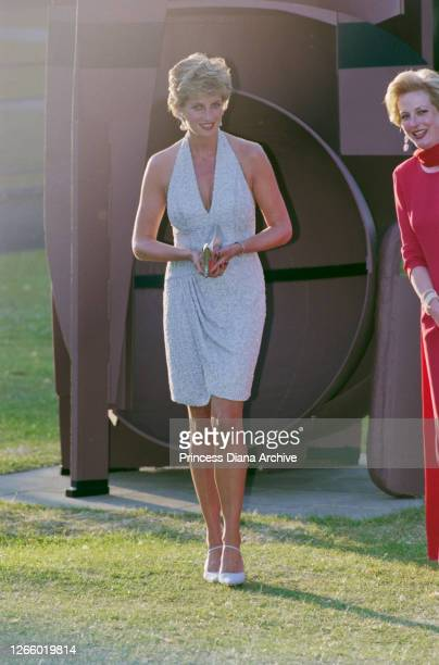 British Royal Diana, Princess of Wales , wearing a pale blue halter-neck dress by fashion designer Catherine Walker, as she attends a dinner hosted...