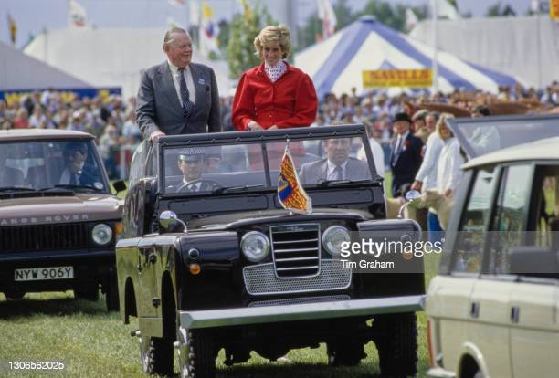 British Royal Diana, Princess Of Wales wearing a red suit, with a red polka dot blouse beneath a peplum jacket, riding with an unspecified man in an...