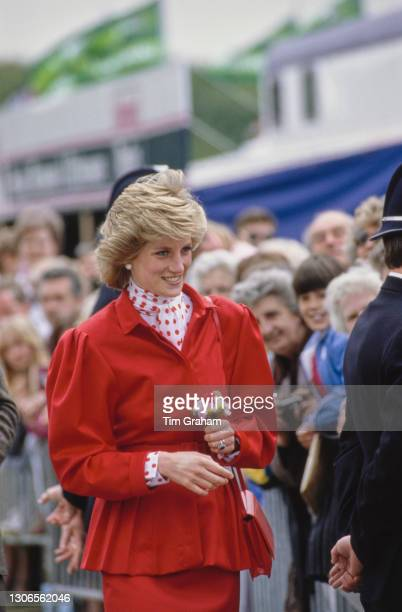 British Royal Diana, Princess Of Wales wearing a red suit, with a red polka dot blouse beneath a peplum jacket, carrying a small bunch of flowers as...